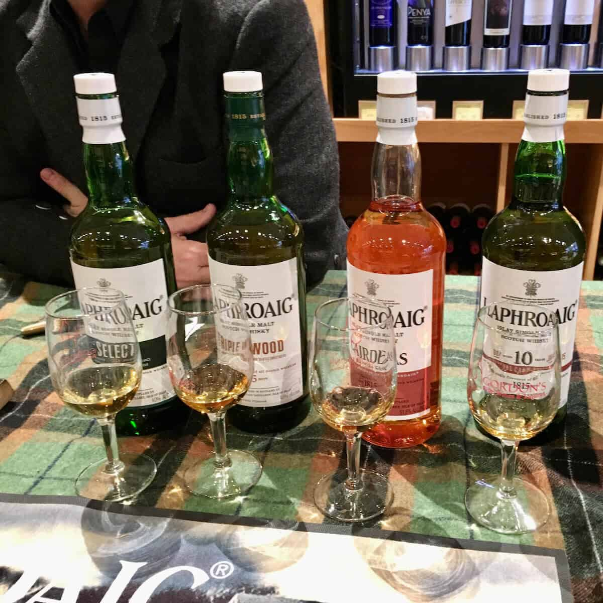 Lineup of Laphroaig scotch whisky poured into glasses with bottles behind on a green checked cloth.