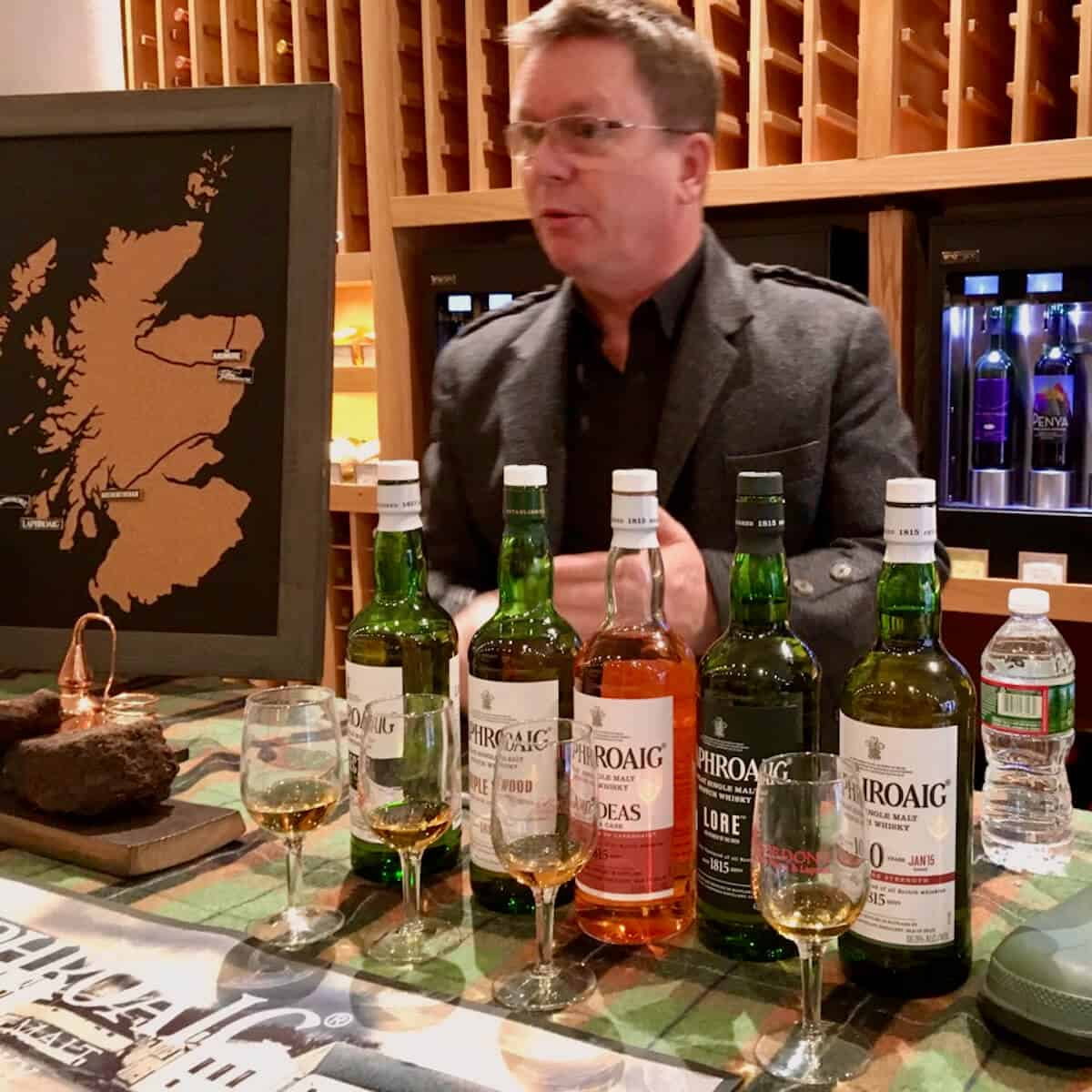 Simon Brooking behind the Laphroaig tasting lineup of glasses & bottles on a green checked cloth.