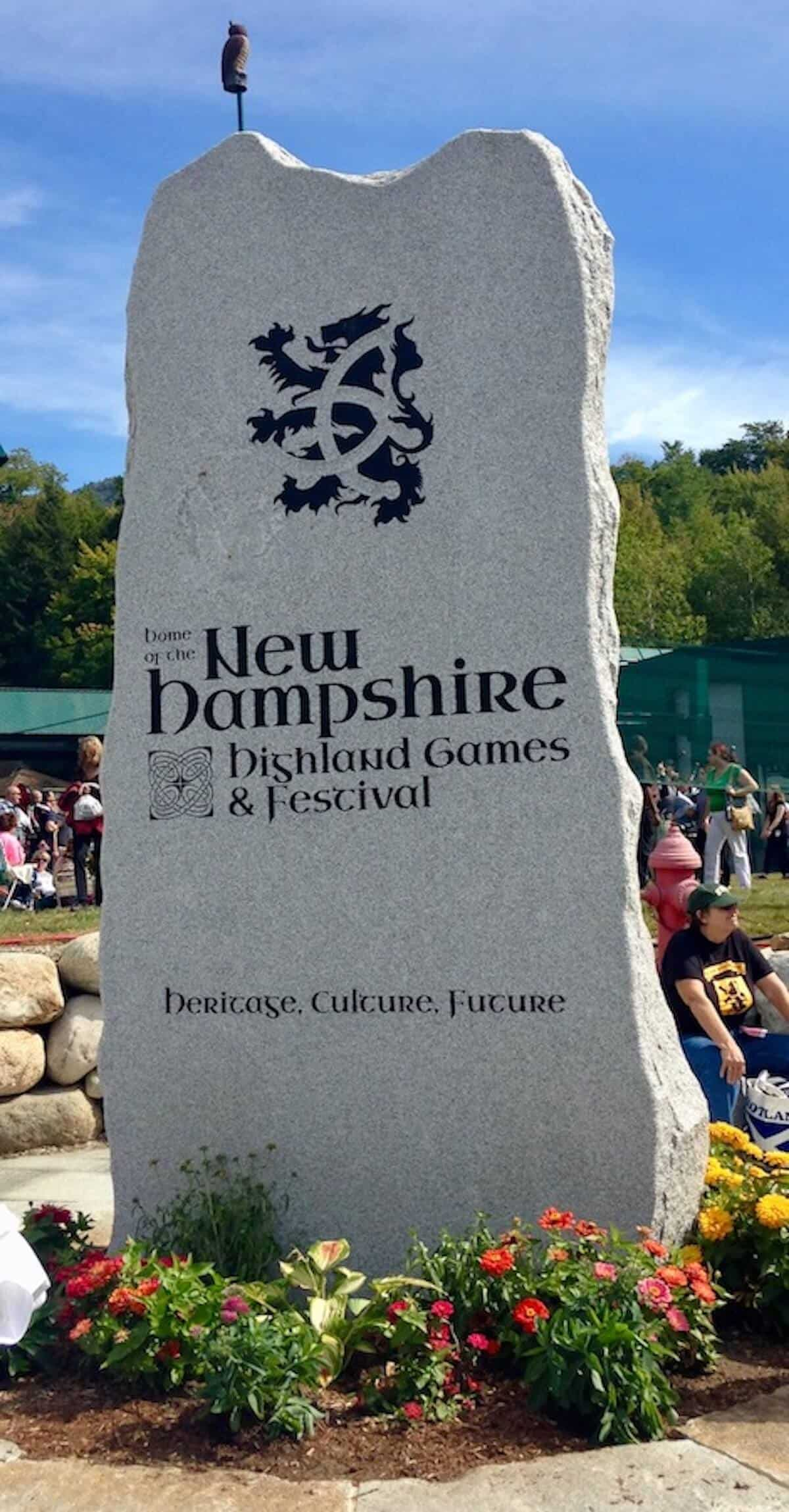 New Hampshire Highland Games & Festival standing stone with flowers at base.
