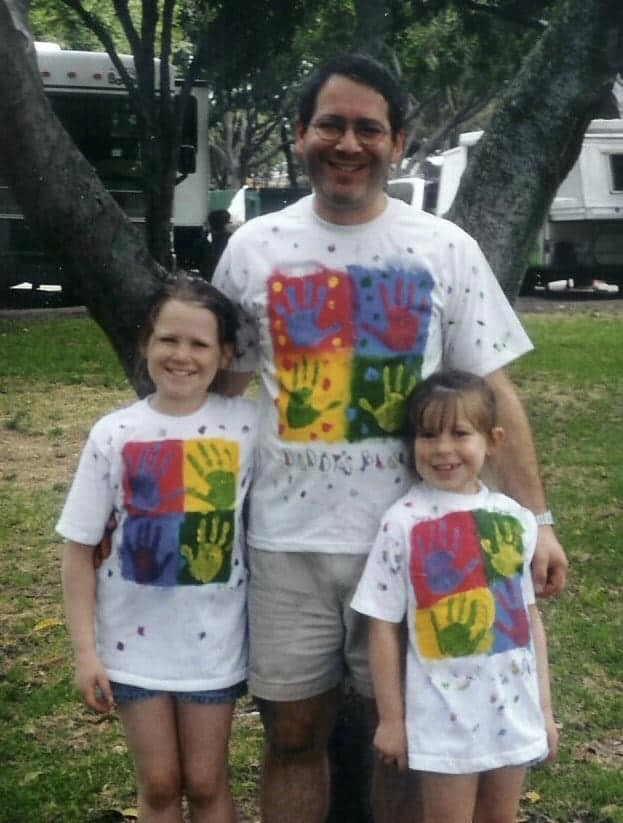 Author's husband and daughters wearing matching Father's Day color block shirts
