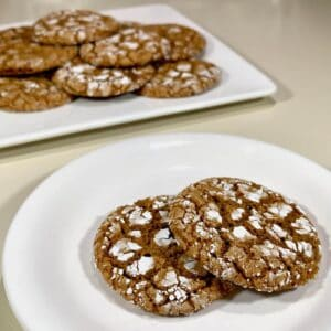 molasses cookies on plate closeup with cookies in background