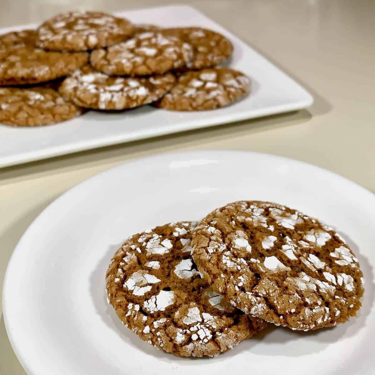 Molasses cookies stacked on a white plate with more cookies in background.