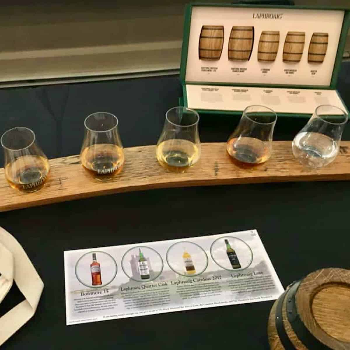 Laphroaig and Bowmore scotch tasting lineup poured in a flight on a table.