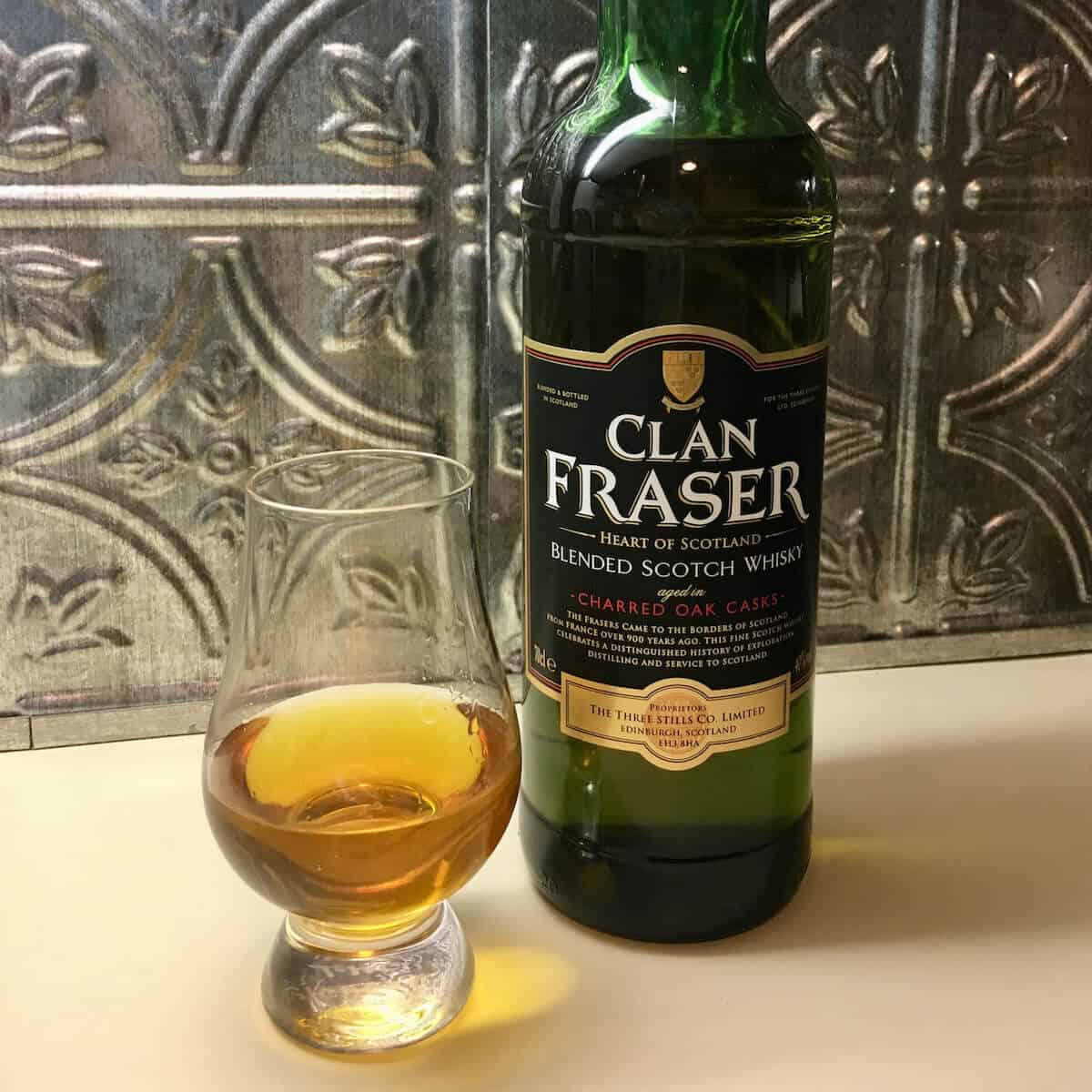 Clan Fraser blended scotch whisky bottle with poured glass.