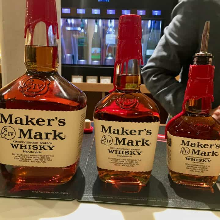 Three sizes of Maker's Mark bottles on a counter.