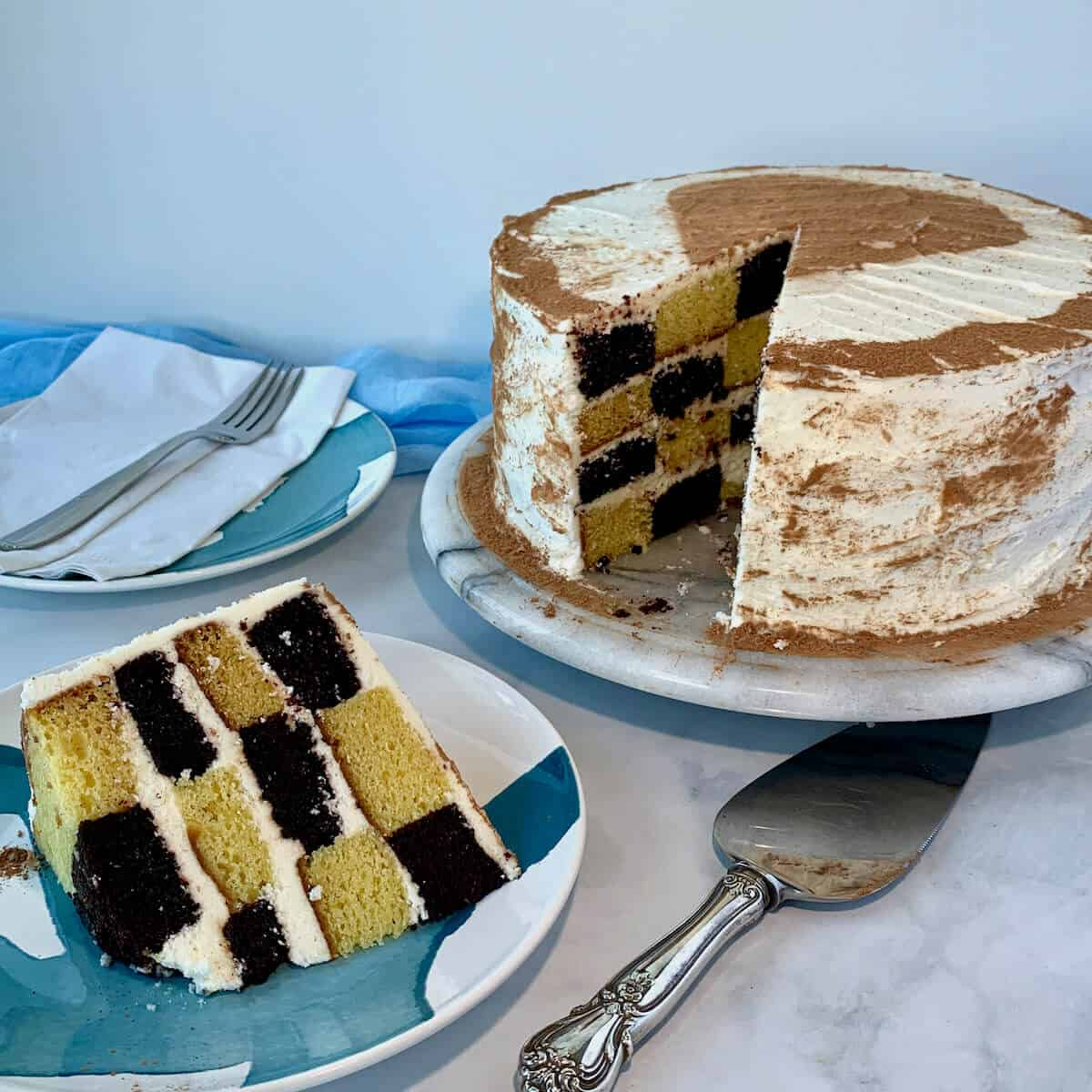 checkerboard cake slice on a blue & white plate next to a cake serve with cake on plate and fork in background