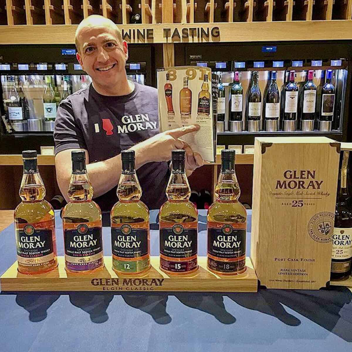 Glen Moray whisky bottle display with sales rep pointing to prochure behind.