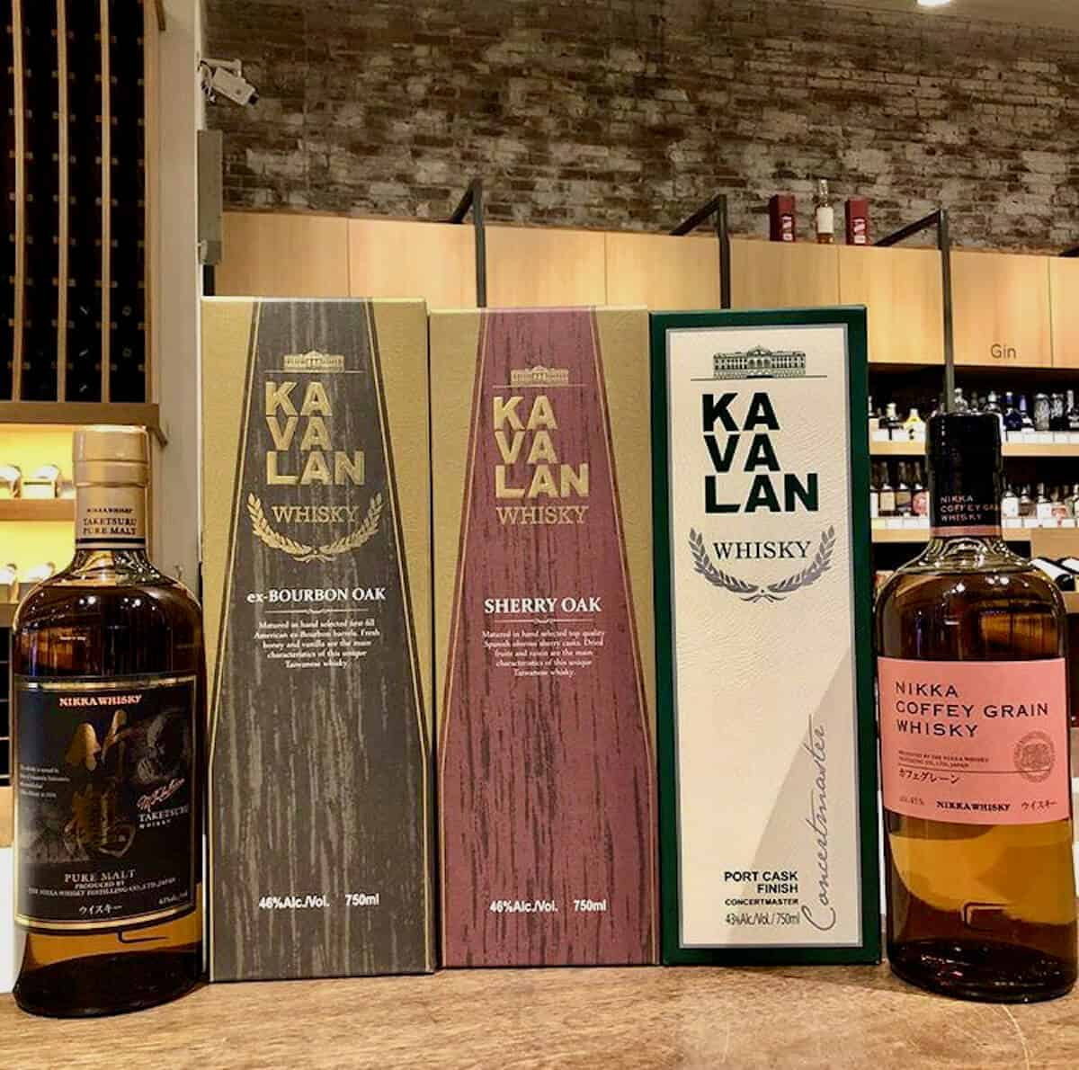 Kavalan & Nikka whisky tasting lineup in boxes on a table.
