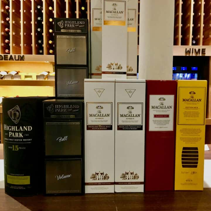 Macallan and Highland Park lineup in boxes on a counter.