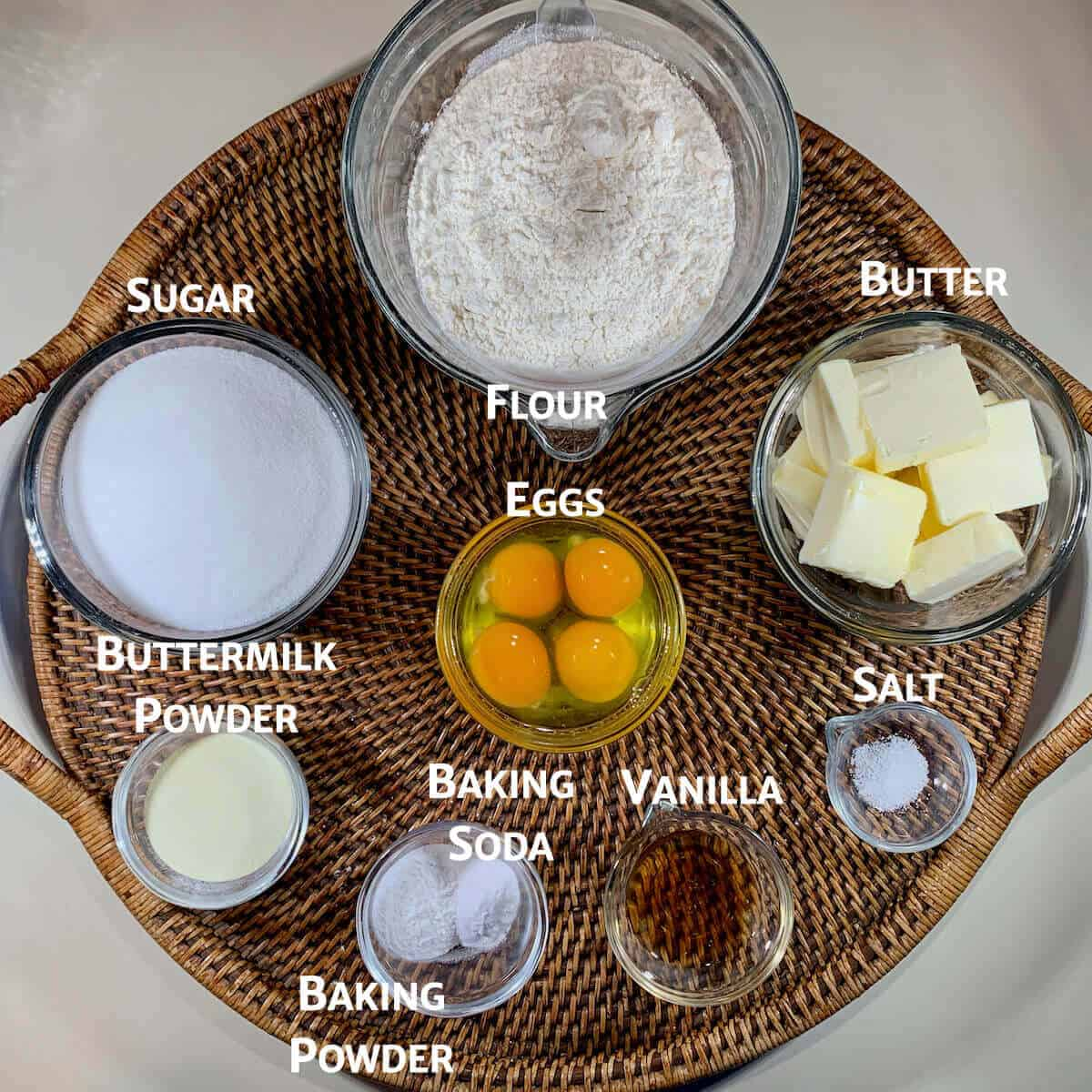 vanilla cake ingredients in glass bowls on a wooden tray