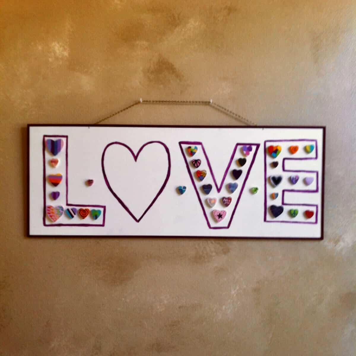 A handpainted sign saying Love hanging on a wall.