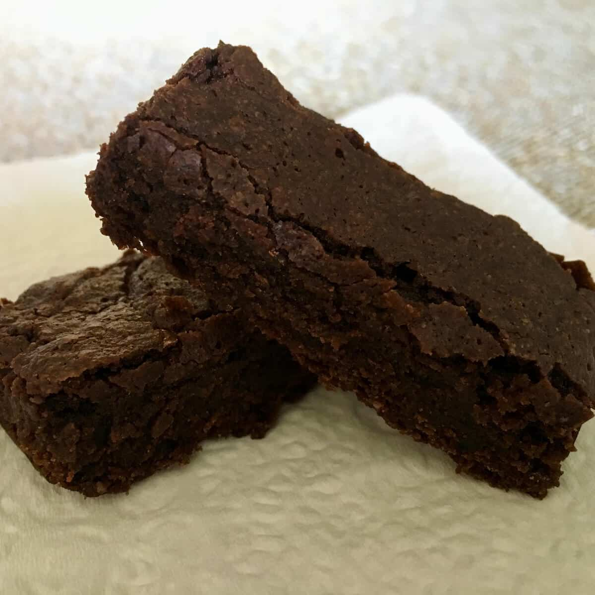 Two bourbon brownies stacked on a napkin.