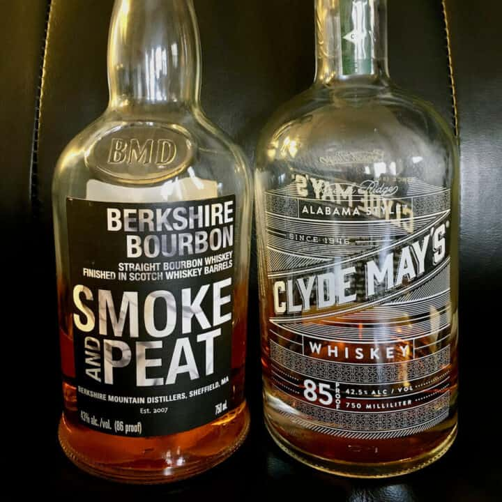 Berkshire Bourbon Smoke & Peat and Clyde Mays Alabama-style whiskey in bottles on a leather chair.