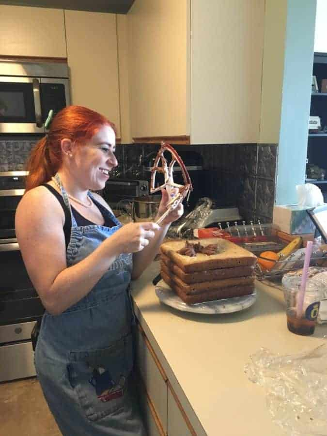 Author's younger daughter frosting and stacking the Chocolate Chip Cookie Cake layers