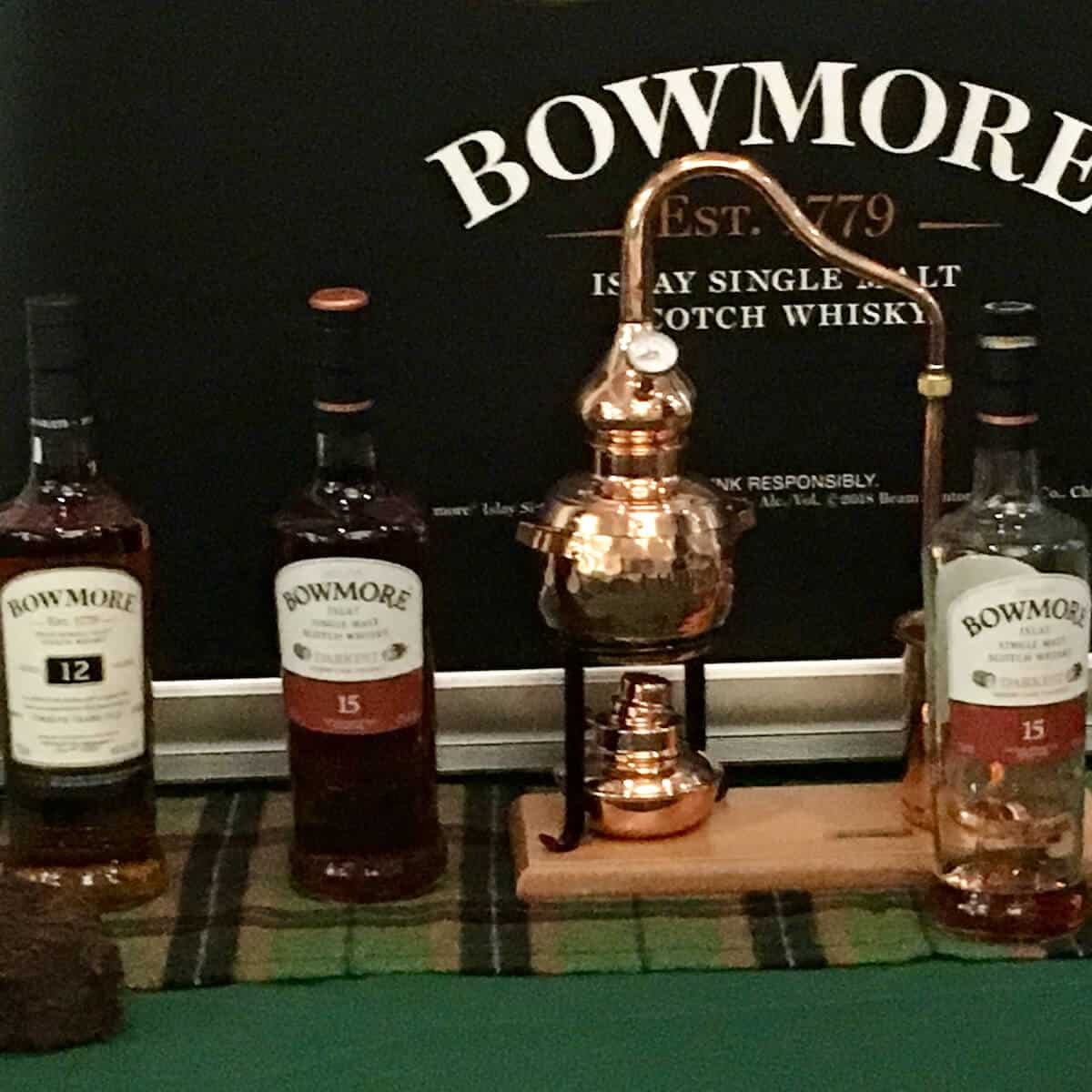 Bowmore lineup in bottles with model of a pot still.