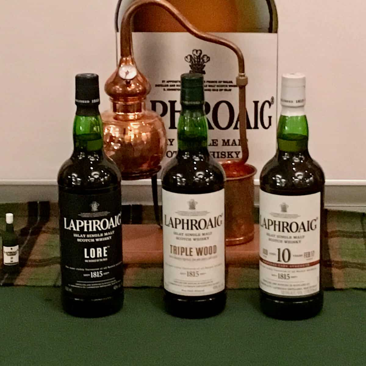 Laphroaig lineup in bottles with model of a pot still.