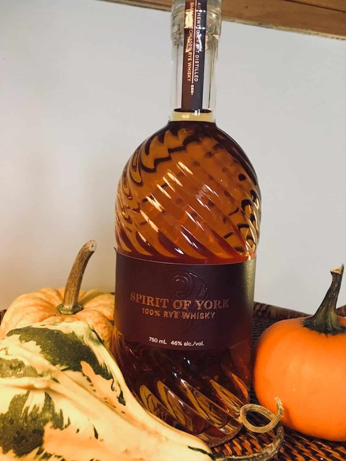 Spirit of York rye whisky bottle surrounded by gourds on a wood tray.Spirit of York rye whisky bottle surrounded by gourds on a wood tray.