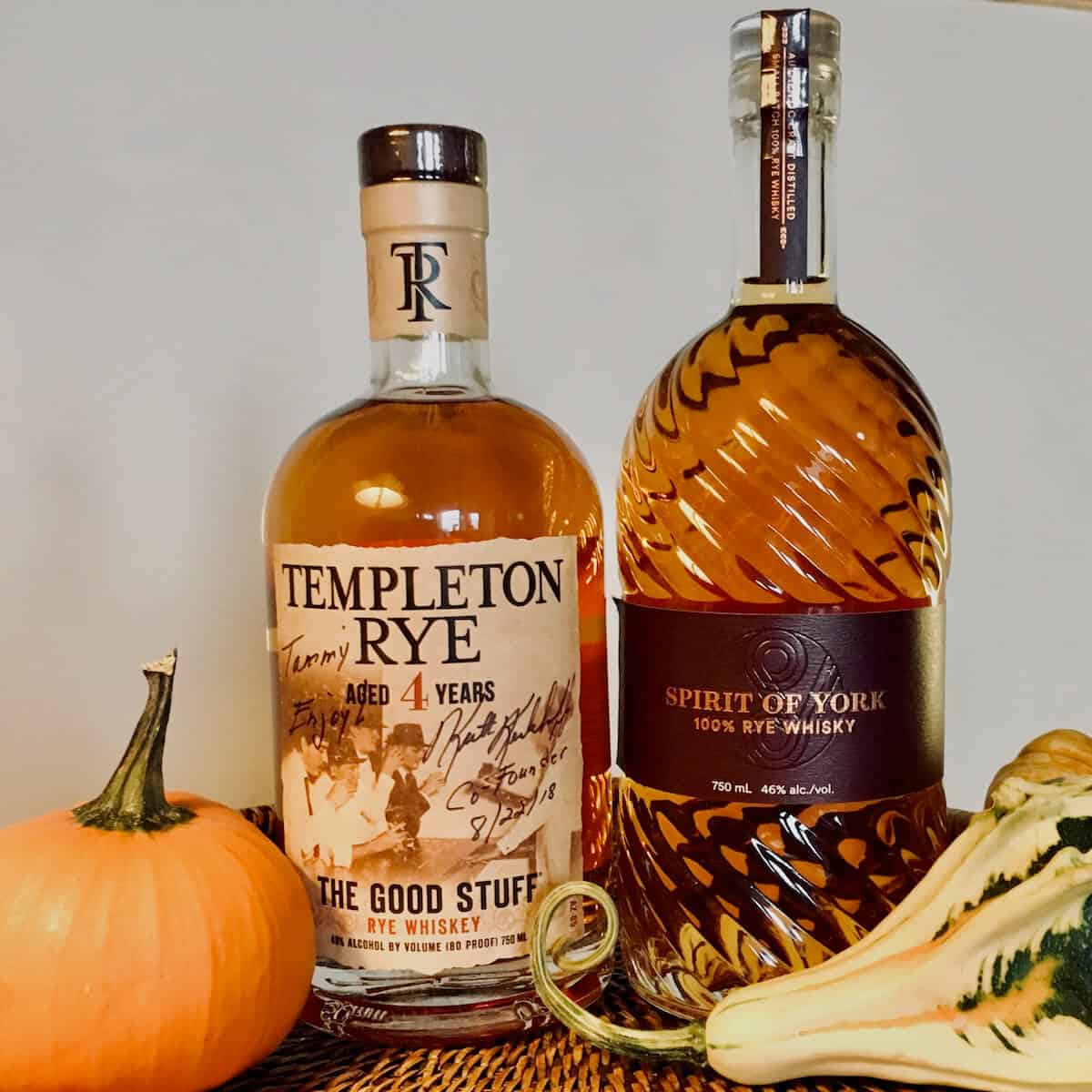 Templeton Rye whiskey and Spirit of York rye bottles surrounded by gourds on a wood tray.