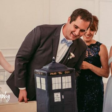 the groom looks over his TARDIS cake