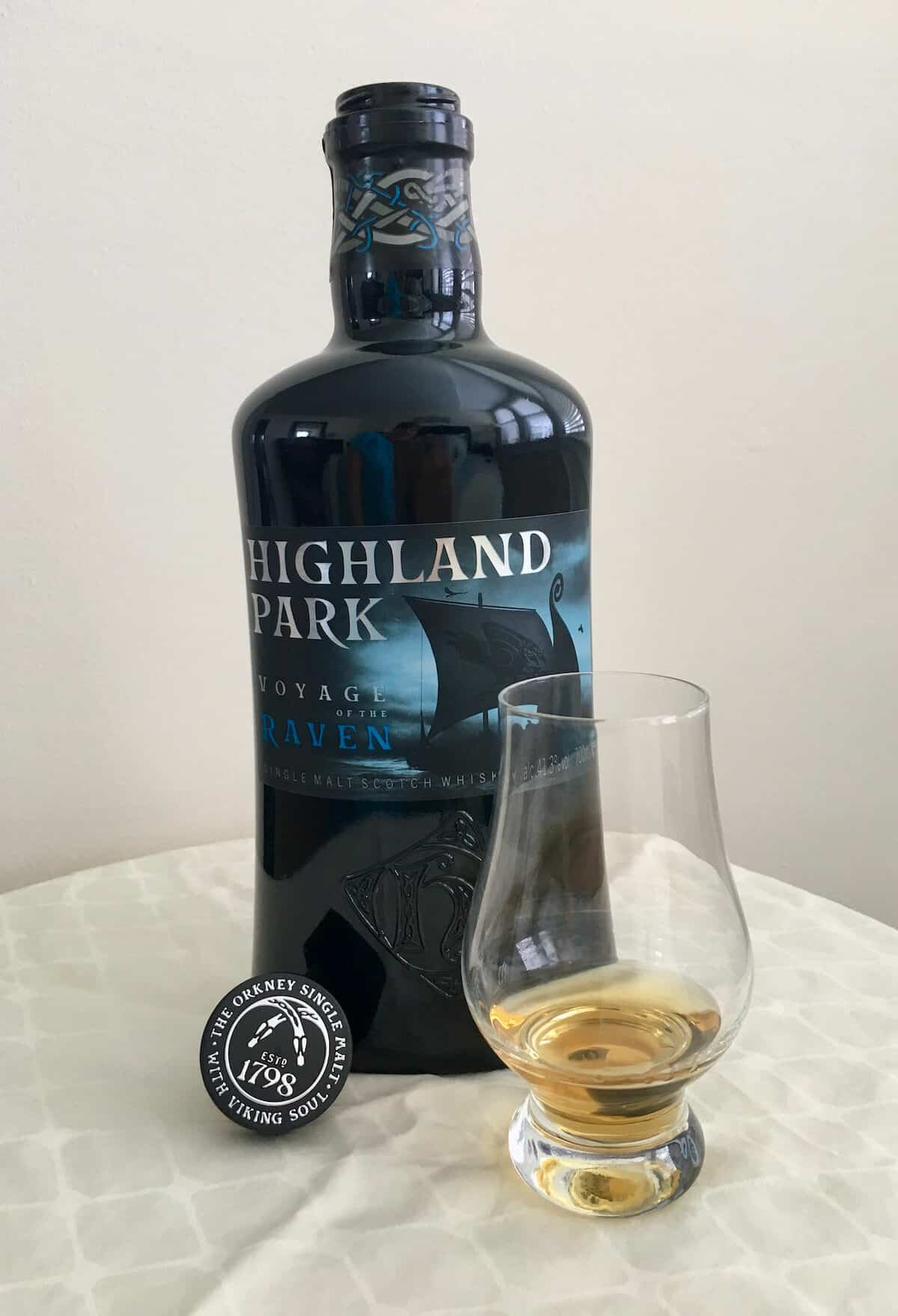 Highland Park Voyage of the Raven in bottle with a poured glass on a table.
