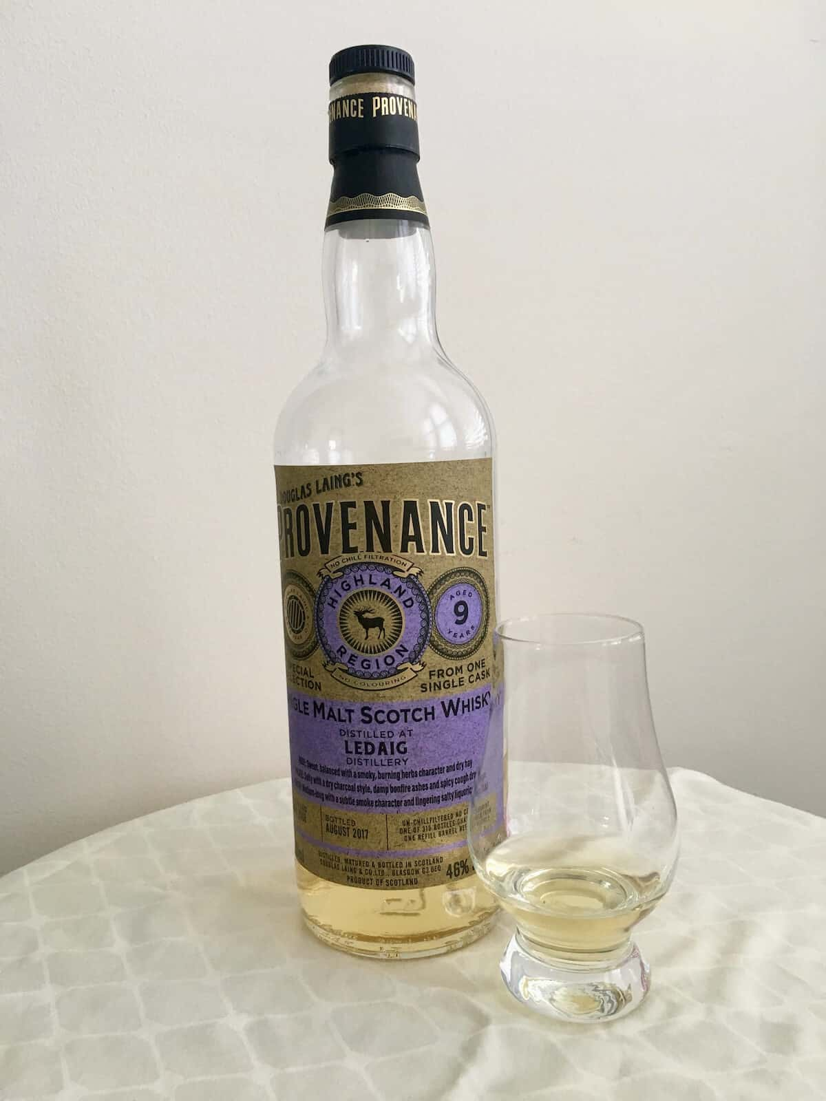 Douglas Laing Provenance in bottle and poured in a glass on a table.