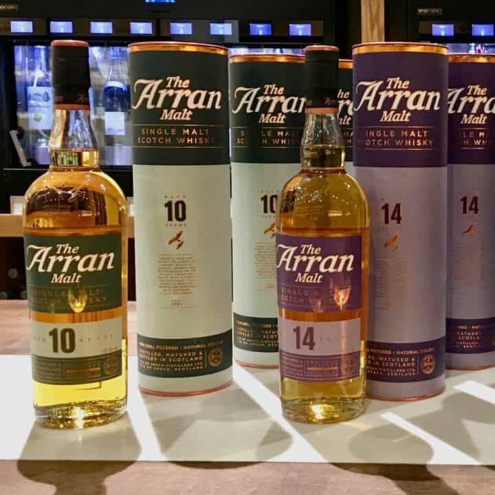 Bottles & sleeves of Arran Malt 10 year and 14 year on a counter