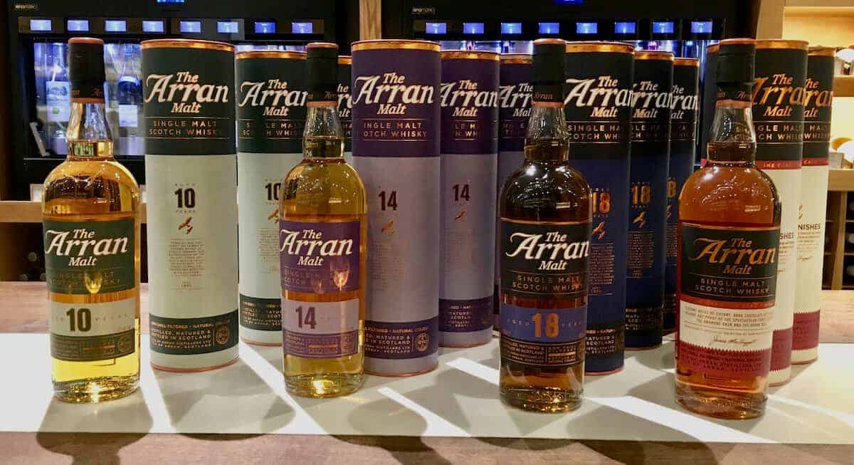 Bottles and sleeves of Arran Malt Collection scotch lineup on a counter.