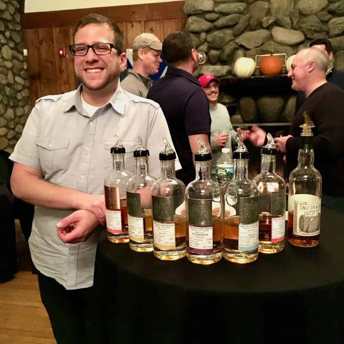 Joshua Hatton with the Exclusive Malts lineup in bottles on a table.