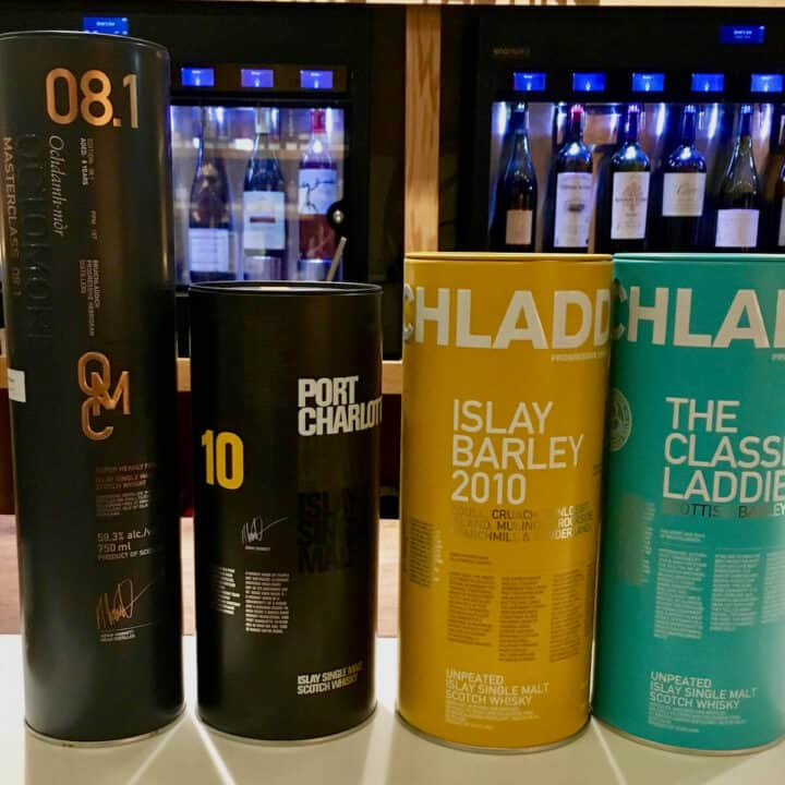 Bruichladdich, Port Charlotte, & Octomore bottle sleeves on a counter.