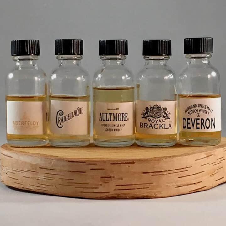 John Dewar & Sons Fine Scotch Whisky Emporium lineup in sample bottles on a wooden tray