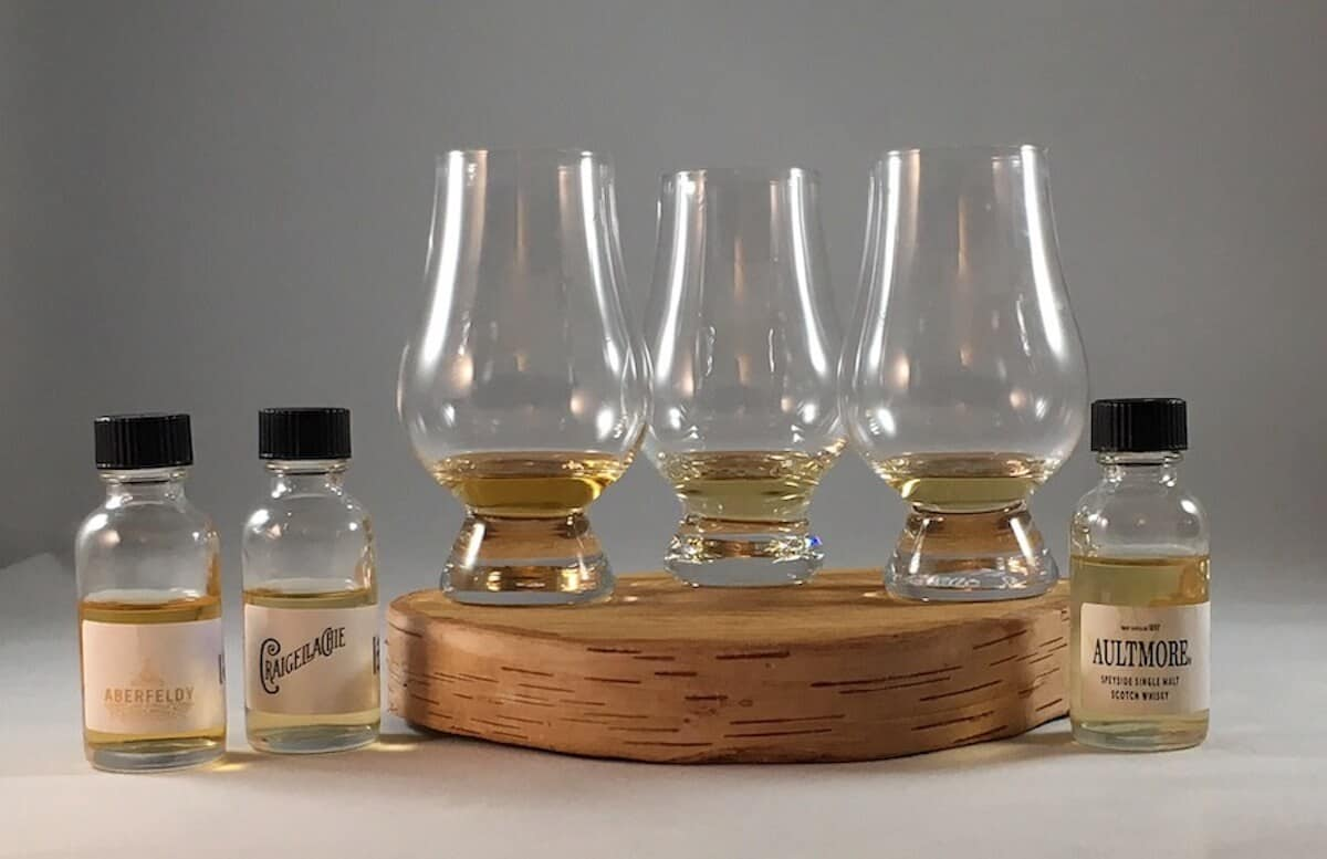 Aberfeldy, Craighellachie, Aultmore in sample bottles beside poured glasses on a wooden tray.