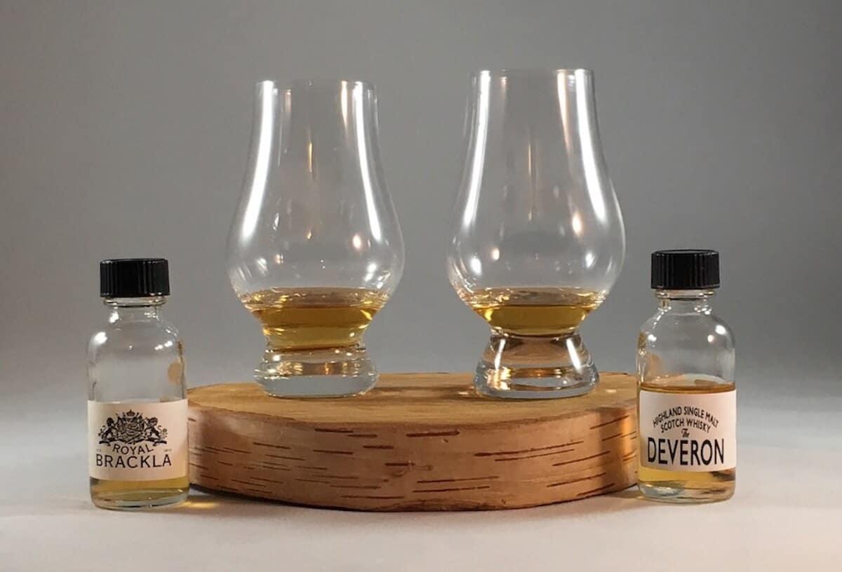 Royal Brackla & Deveron in sample bottles beside poured glasses on a wooden tray.