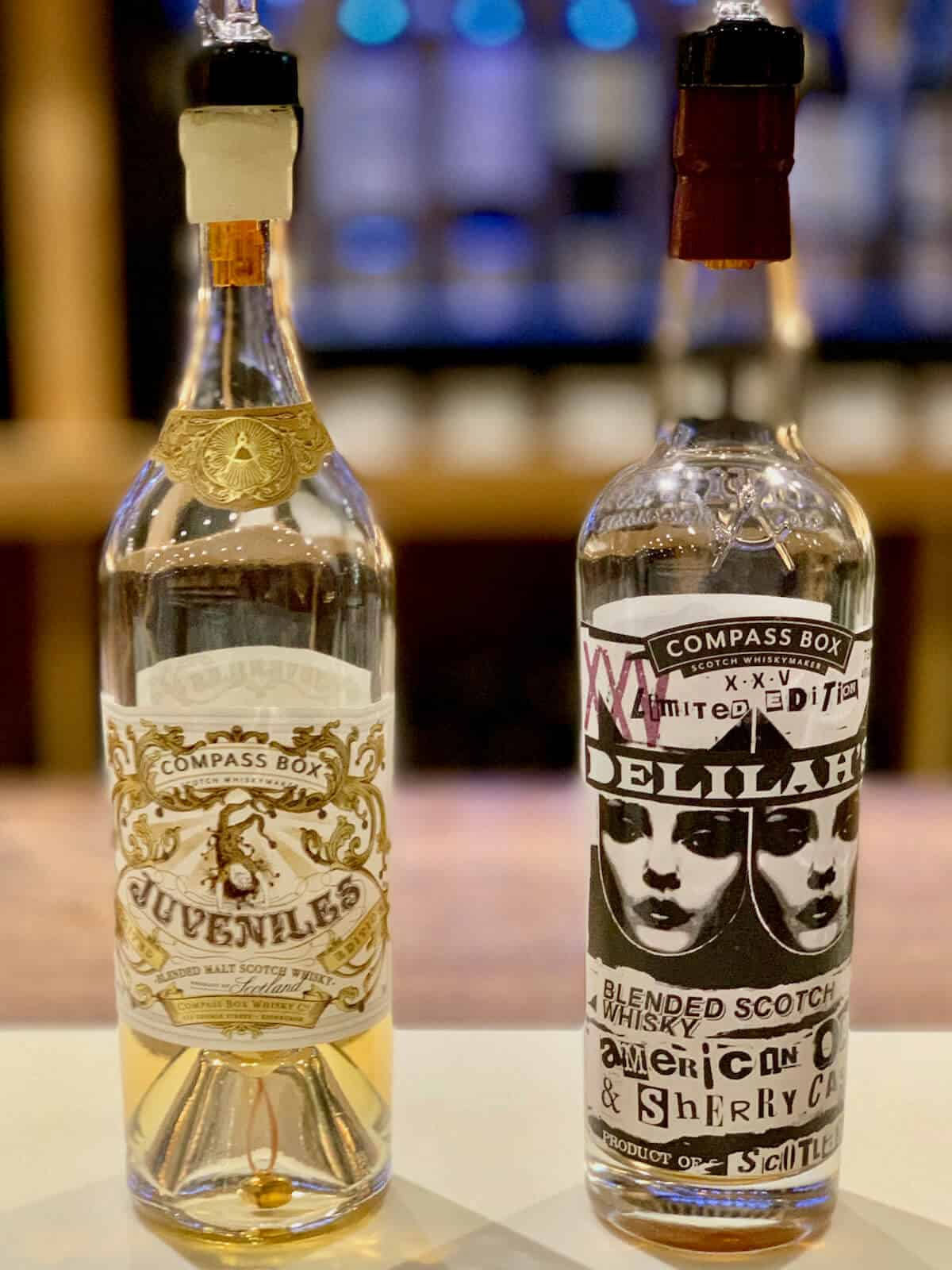 Compass Box Blended Scotch Juveniles and Delilah 25 in bottles on a counter.