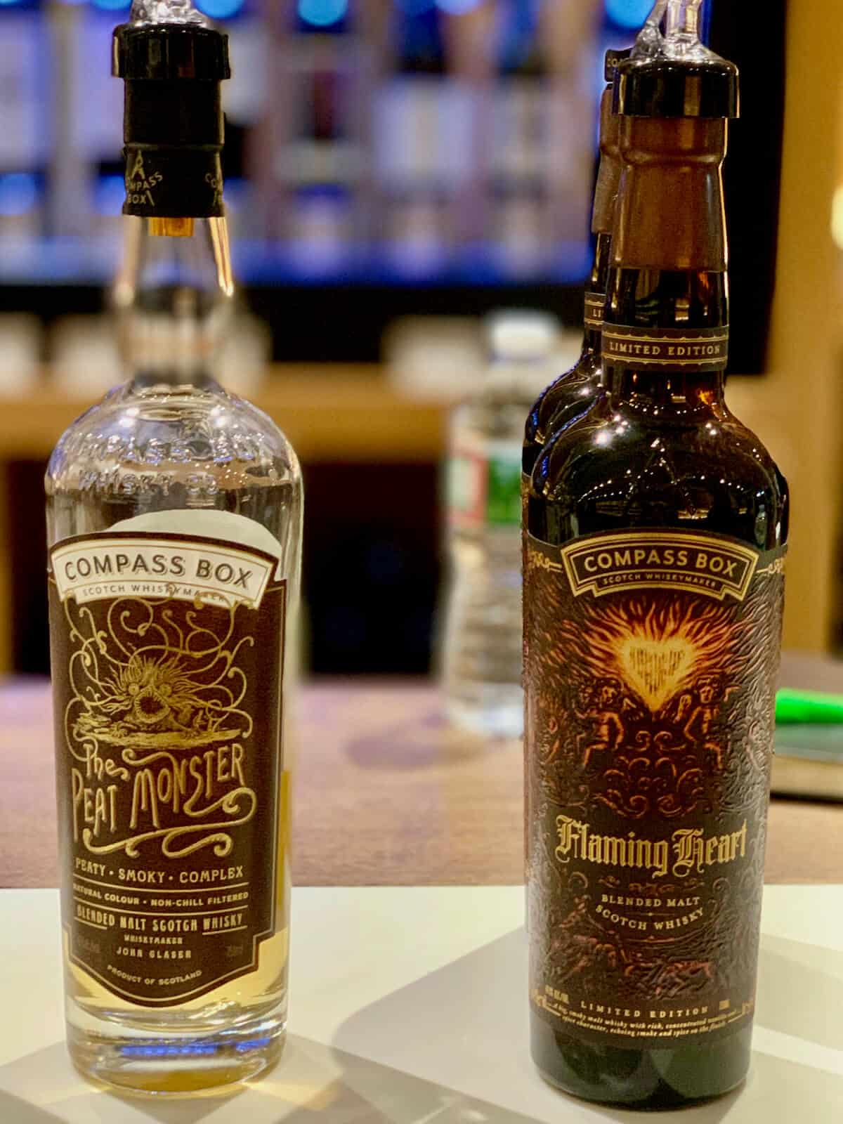 Compass Box Blended Scotch Peat Monster and Flaming Heart in bottles on a counter.
