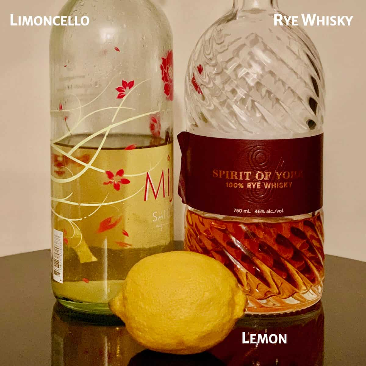Limoncello Rye Sour ingredients - Homemade Limoncello & Spirit of York Rye Whiskey in bottles with a lemon