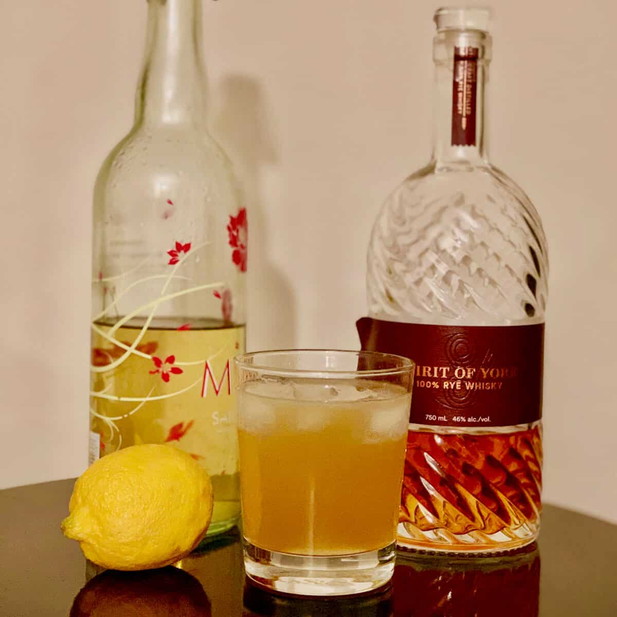 Limoncello Rye Sour ingredients - Homemade Limoncello & Spirit of York Rye Whiskey in bottles with a lemon and drink in glass