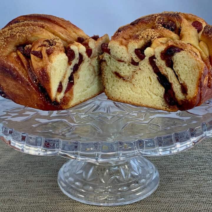 Cranberry Wine Babka split open on a glass cake stand.