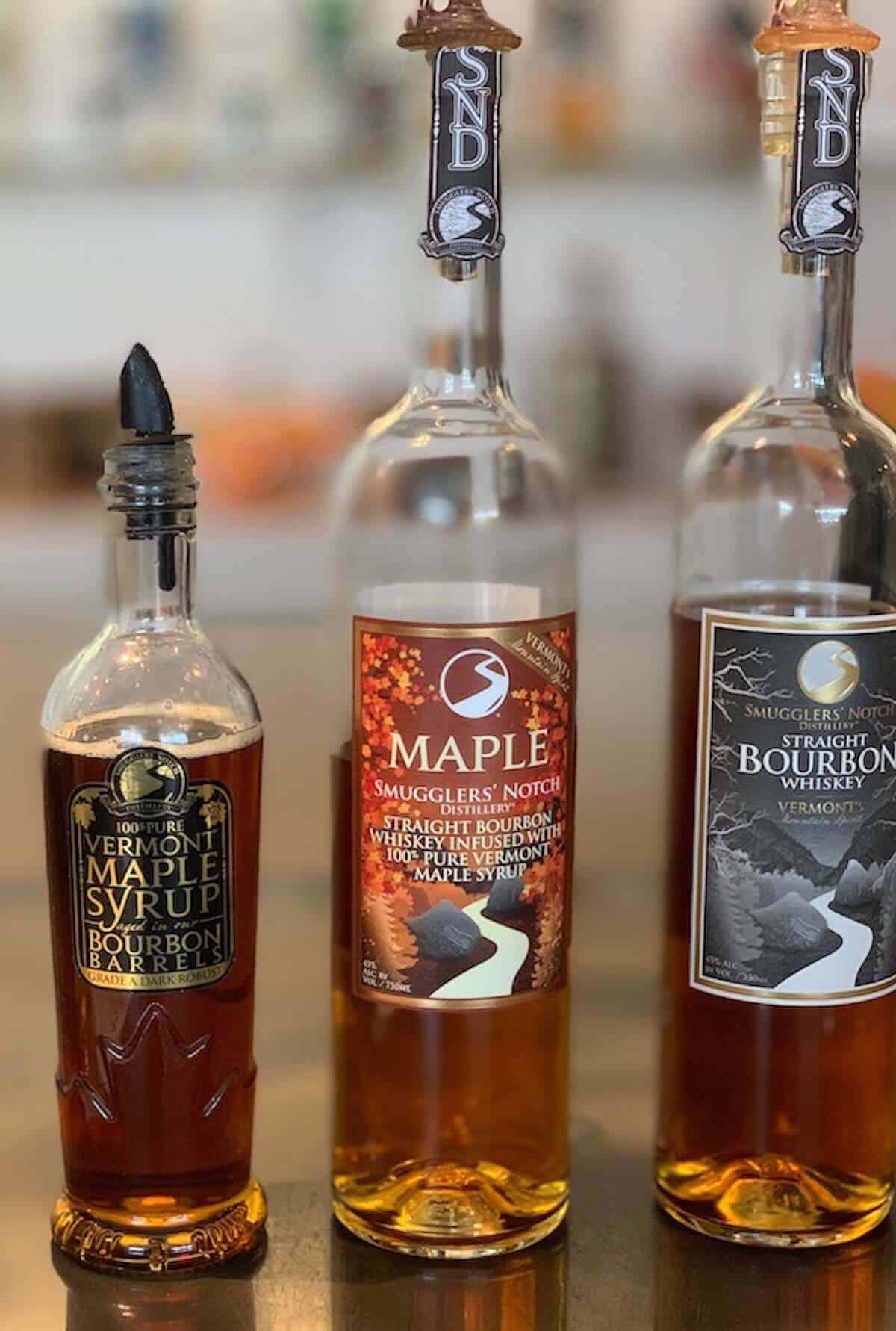 Smugglers' Notch Distillery maple syrup, maple bourbon, & straight bourbon on counter.