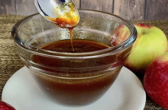 boiled apple cider dripping from spoon