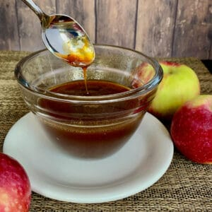 Boiled apple cider dripping from a spoon into a glass bowl on a white plate with apples.