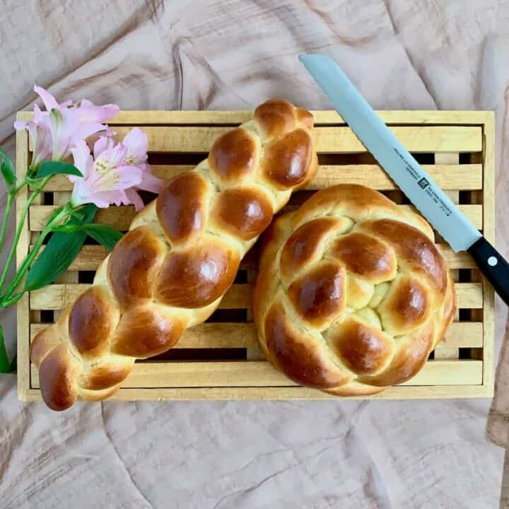 oblong 4-strand and round 4-strand challah on cutting board with knife overhead