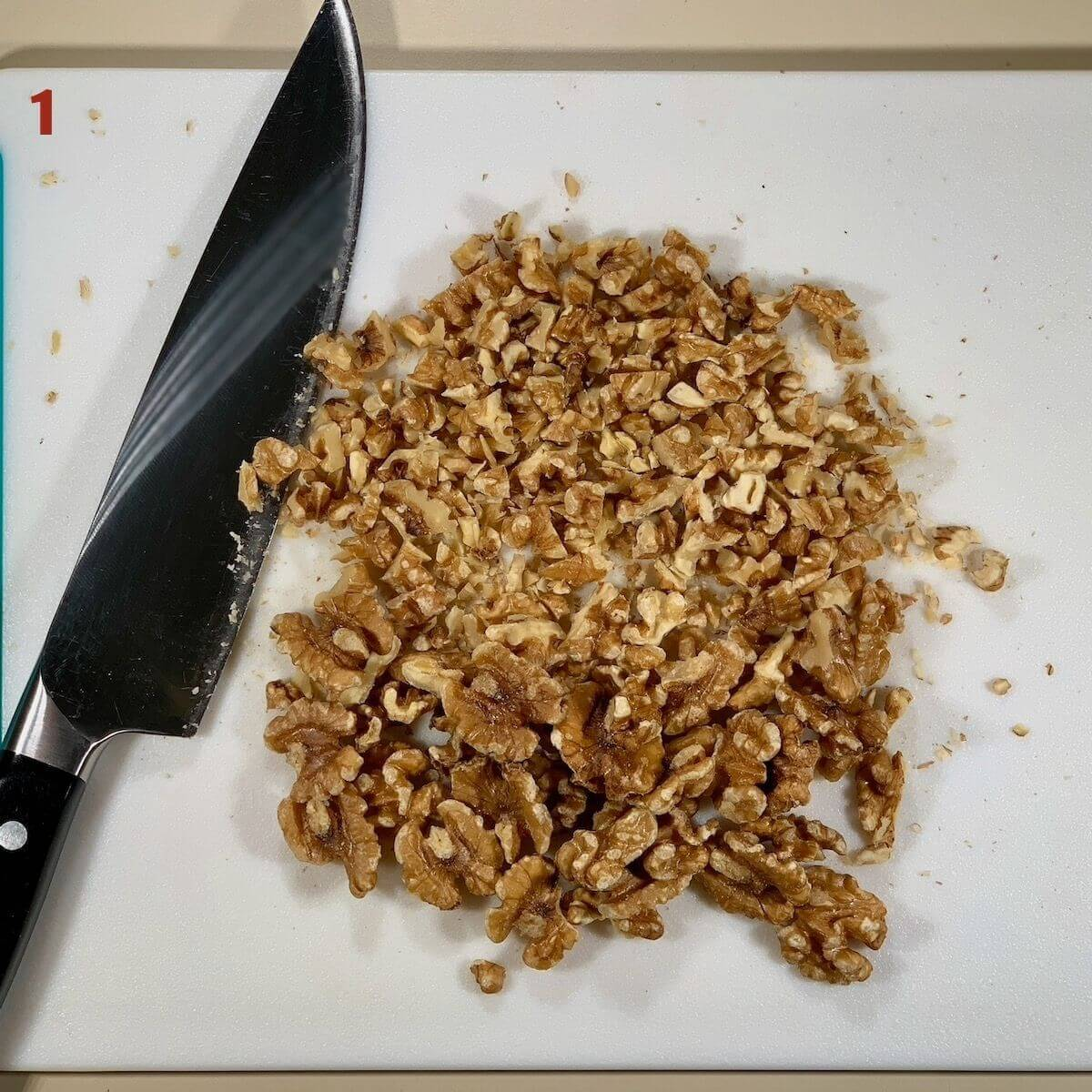 Chopped walnuts on a cutting board with knife.