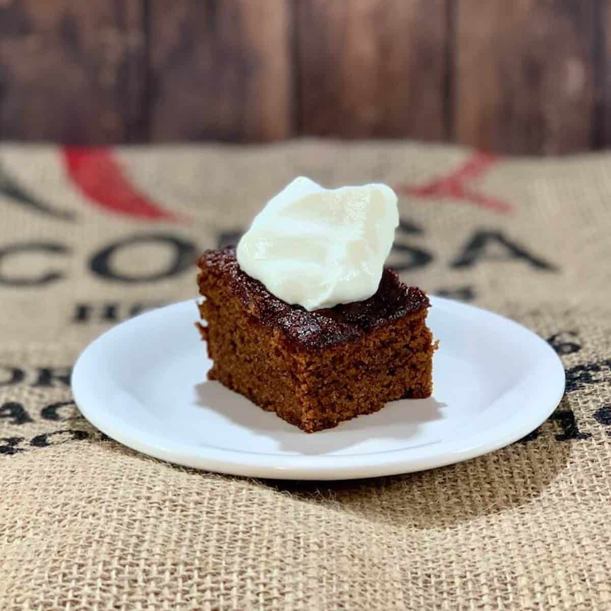 Sourdough gingerbread plated with whipped cream.