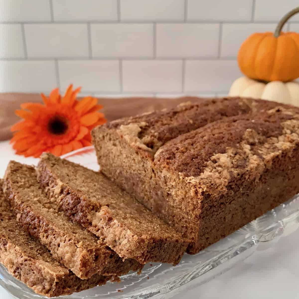 Sourdough Spice Cake sliced on plate with pumpkins.