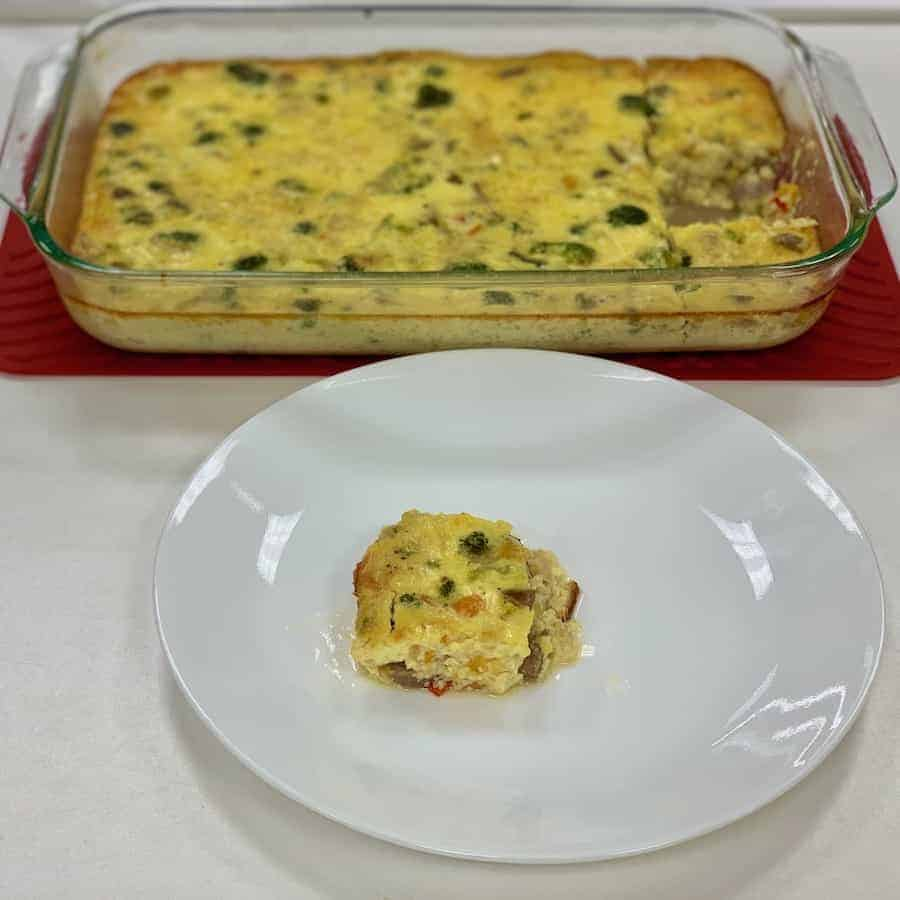 Chicken Sauce & Broccoli crustless quiche slice plated with full baking dish in background