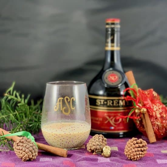 glass of homemade eggnog with the brandy bottle & festive greenery