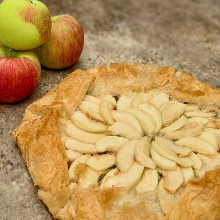 Apple galette with apples on a brown background.