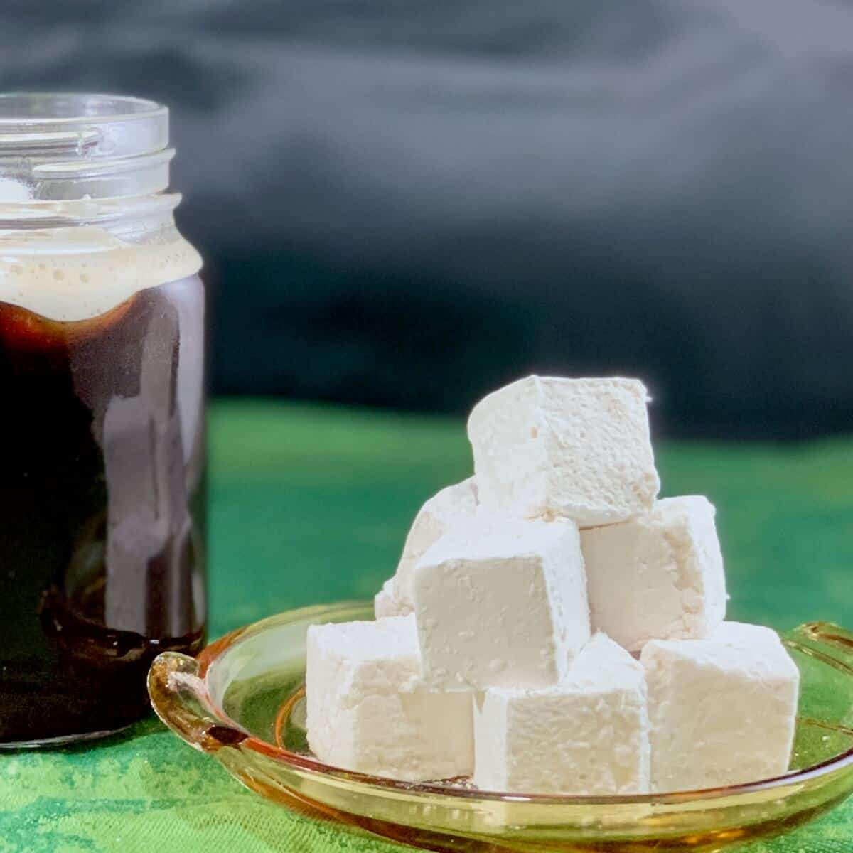 Irish Whiskey Marshmallows stacked on plate closeup with Irish coffee in background.