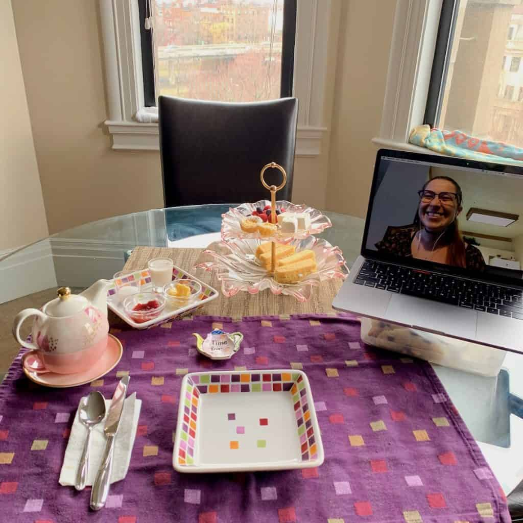 A table setting of High Tea plus a laptop with a FaceTime image