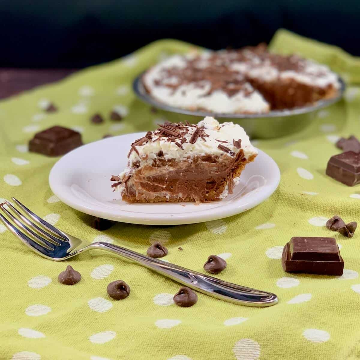 Chocolate Cream Pie slice on a white plate with fork & chocolate on a green polka dot towel.